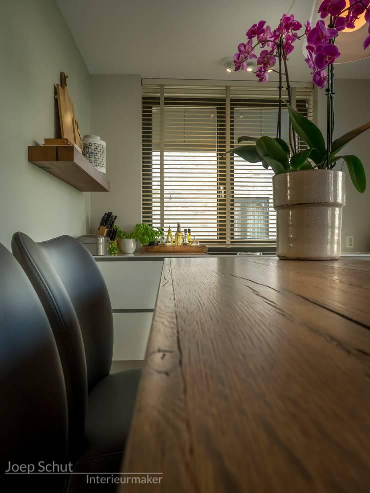 Maatwerkkeuken met eiland -composietwerkblad en kastenwand van Oak vintage Hoboken fineer: modern  door Joep Schut, interieurmaker, Modern