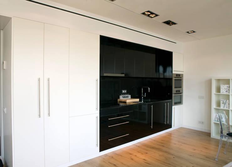 Cocina negra en comedor de pared y armarios blancos con suelo de madera.: Escaleras de estilo  de projectelab