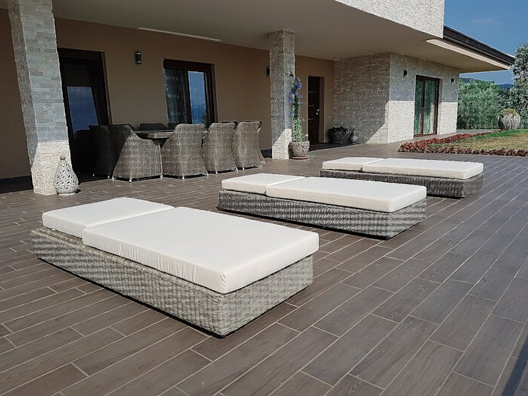 Sdraio da giardino di design Sulawesi e tavolo dieci posti in fibra sintetica tonda Uluwatu: Giardino in stile  di Uniko