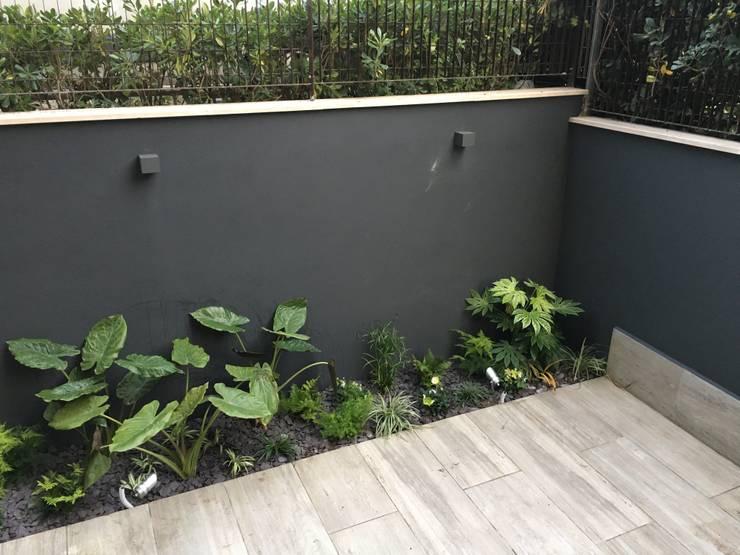 Jardines en la fachada de estilo  por Au dehors Studio. Architettura del Paesaggio