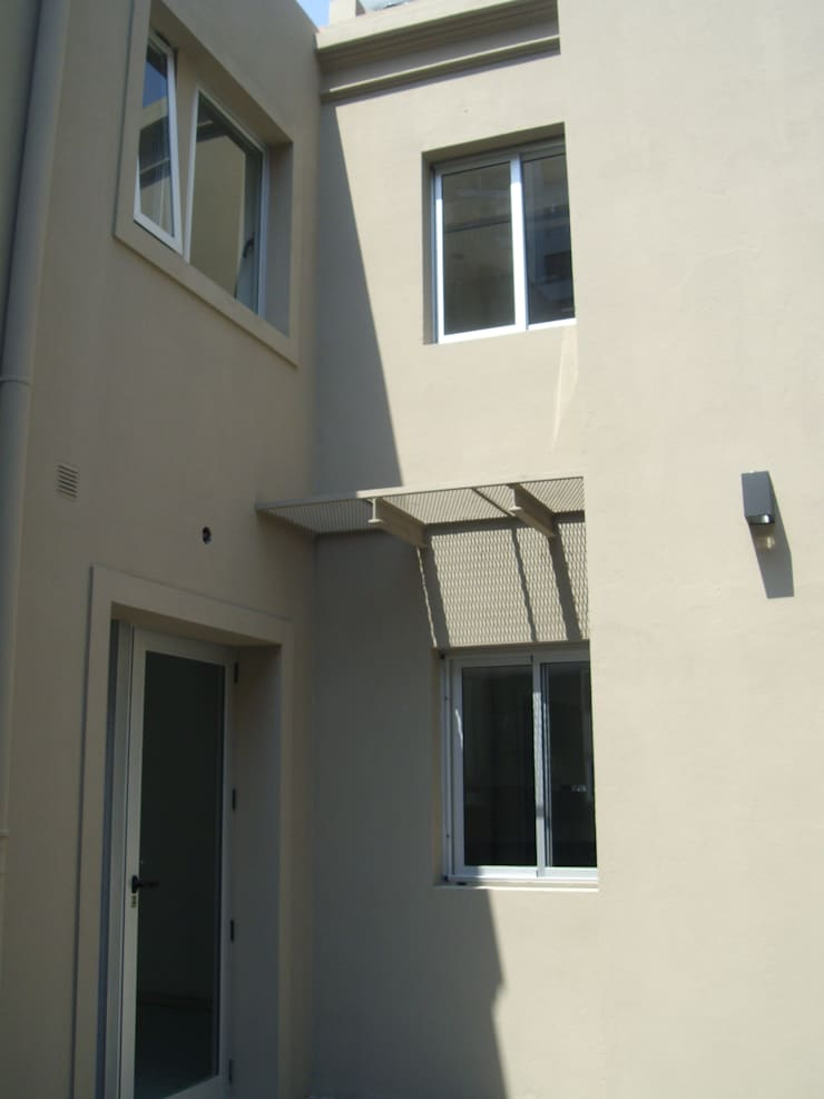 Casa Chenaut - Patio de acceso. : Jardines en la fachada de estilo  por NG Estudio,Moderno Caliza