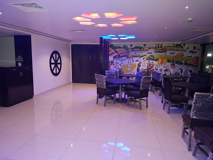 Resturant design with tables and chairs:   by Interior Axis India Pvt,Ltd