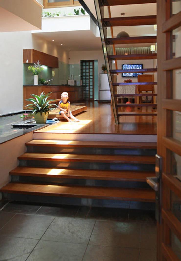 Giếng trời giữa nhà giúp ánh sáng có thể chiếc tới các phòng.:  Hành lang by Công ty TNHH Thiết Kế Xây Dựng Song Phát