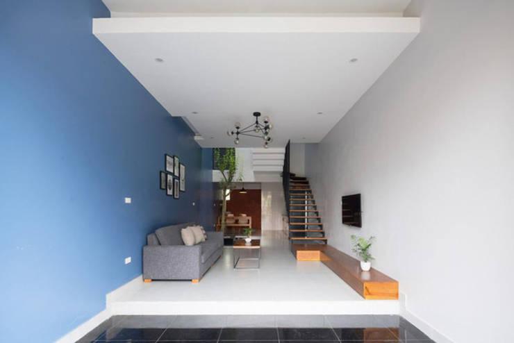 Tại tầng 1, gia chủ dành không gian làm nơi để xe, đón tiếp khách khứa.:  Phòng khách by Công ty TNHH Thiết Kế Xây Dựng Song Phát