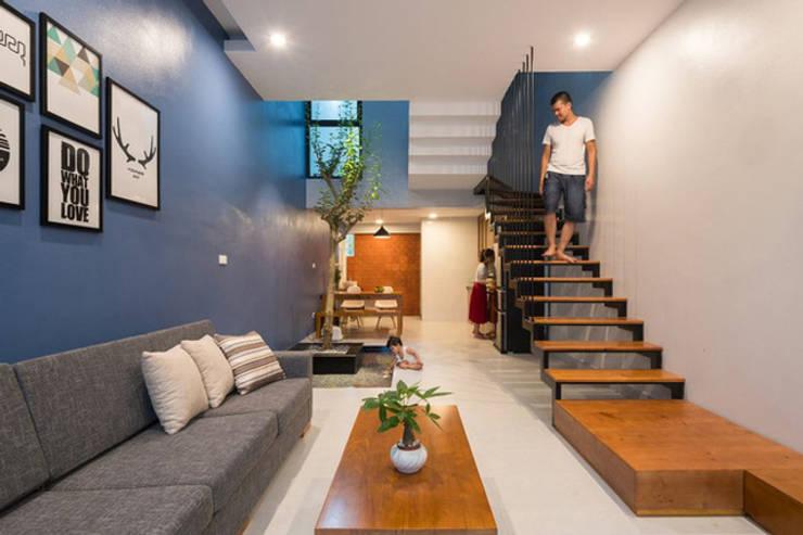 Cầu thang trong nhà được xoay hướng khác so với lối thiết kế truyền thống.:  Phòng khách by Công ty TNHH Thiết Kế Xây Dựng Song Phát