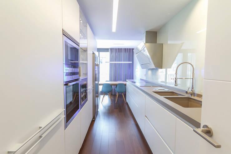 Diseño de la cocina moderna en cerámica blanca y suelo laminado oscuro: Cocinas de estilo moderno de Muka Design Lab
