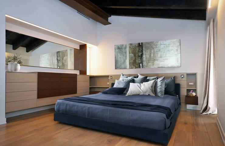 Una mansarda con soffitti in legno e arredamento moderno a brescia