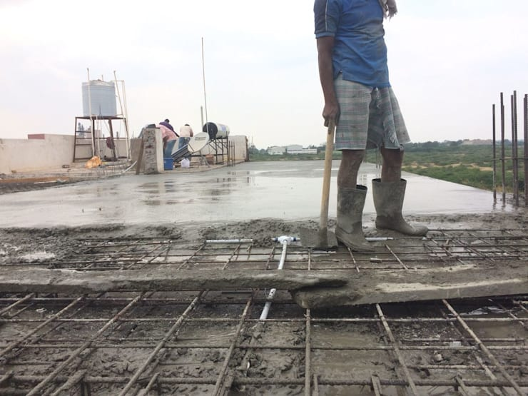 Concrete pouring for slab in progress:  Single family home by Cfolios Design And Construction Solutions Pvt Ltd,Modern