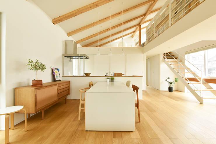 ひと続きの勾配天井で一体感のある空間: タイコーアーキテクトが手掛けたダイニングです。,モダン