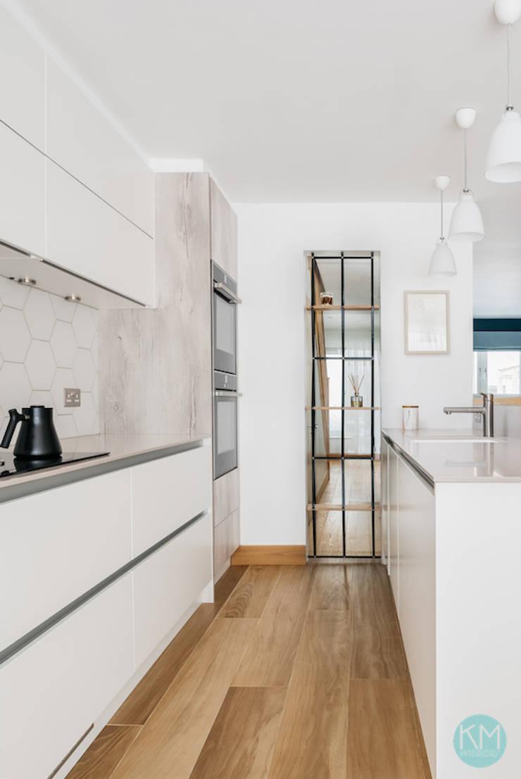 Scandinavian style open kitchen with a breakfast bar:  Kitchen by Katie Malik Interiors