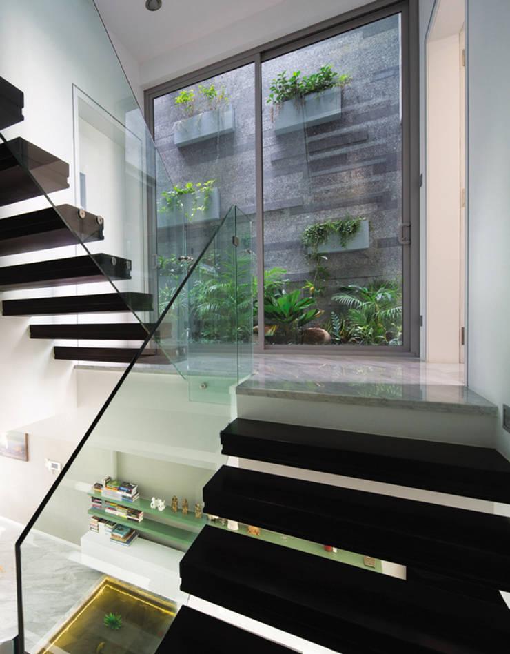 Ô kính rộng được bố trí tại khu vực cầu thang hướng ra khu vườn phía sau.:  Cầu thang by Công ty TNHH Thiết Kế Xây Dựng Song Phát