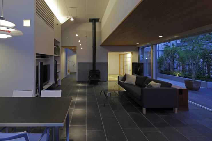 ミドセンチュリーテイスト 居間がテラスと一体化して繋がる成城の住まい: JWA,Jun Watanabe & Associatesが手掛けたリビングです。