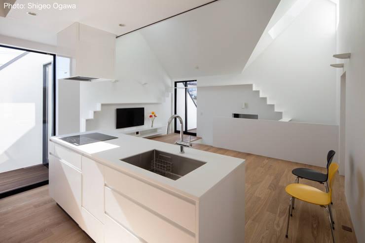 オーダーキッチンとリビング: 石川淳建築設計事務所が手掛けたシステムキッチンです。