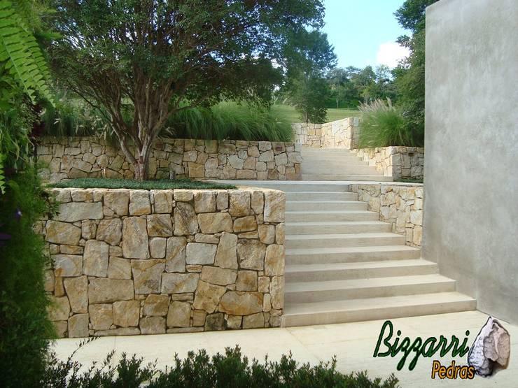 Muro e escada de pedras no jardim : Jardim  por Bizzarri Pedras