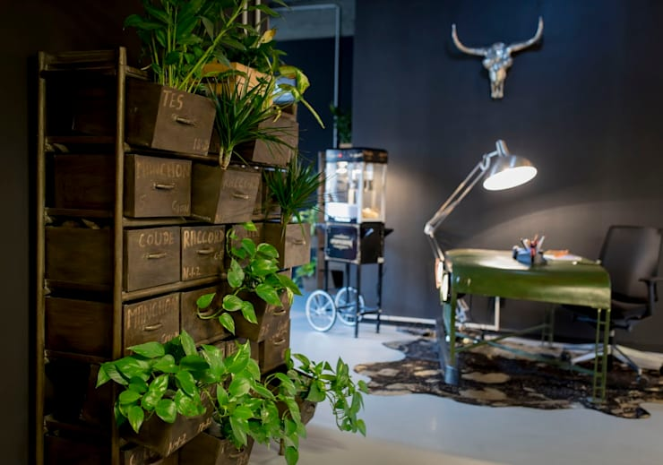 A vintage drawer as plant holder, a cow rug and an old car part reception desk Ausgefallene Arbeitszimmer von Ivy's Design - Interior Designer aus Berlin Ausgefallen Plastik