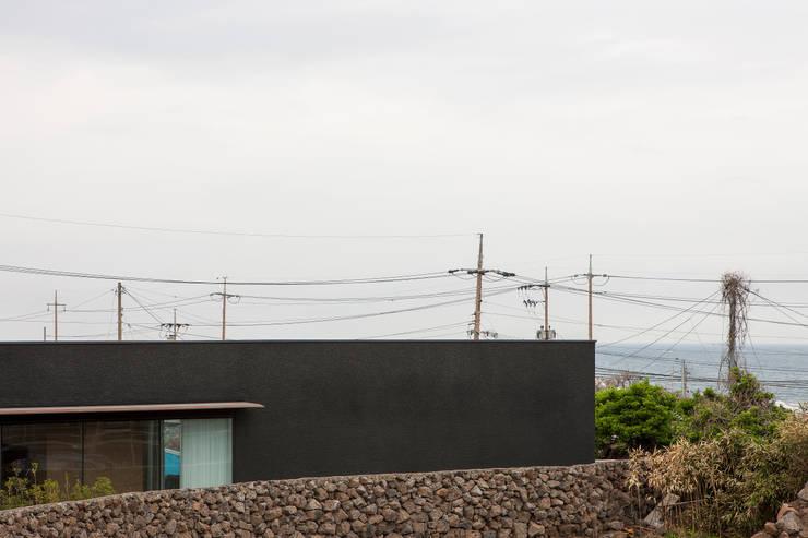 건축의 동쪽면, 건축과 돌담과 바다의 수평.: 백에이어소시에이츠의  주택