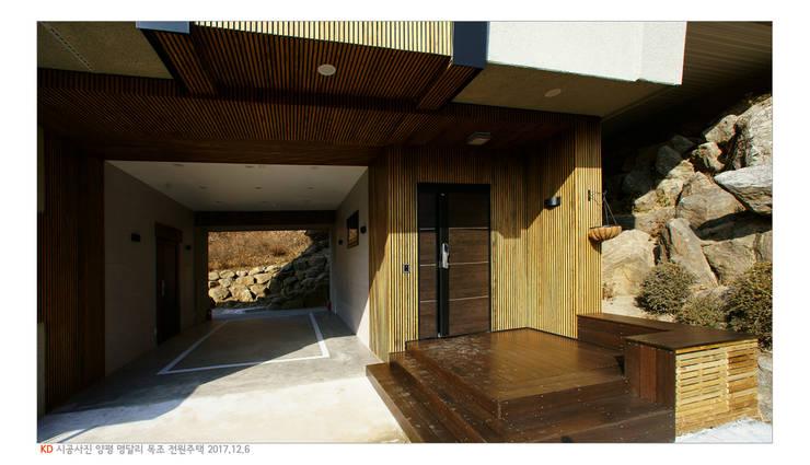 KD탄화목 Thermowood  외장재 시공현장  / 양평 전원주택 /현관과 주차장: 케이디우드테크 의  주택
