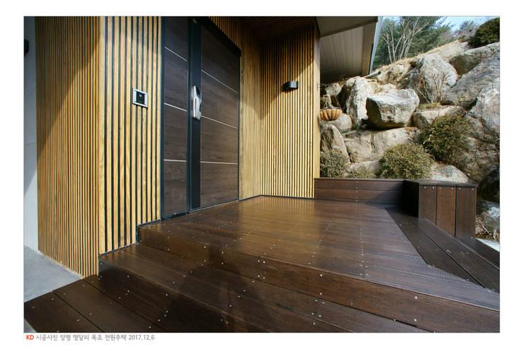KD탄화목 Thermowood  외장재 시공현장  / 양평 전원주택 / 현관 주변과 데크 : 케이디우드테크 의  주택