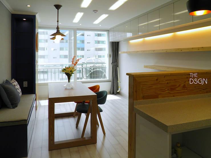 상부장으로 띄지 않는 수납과 붙박이형 소파로 공간을 살린 거실: 더디자인 the dsgn의  거실