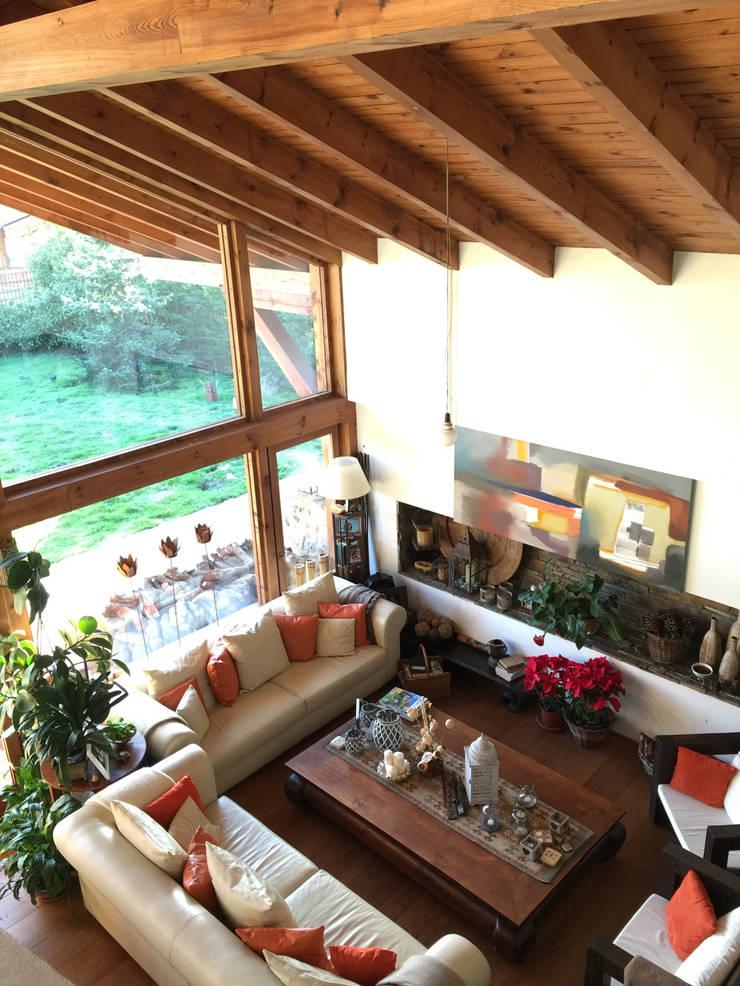 La casa del tejado hasta el suelo. Becerril de la Sierra, Madrid: Salones de estilo rústico de Manuel Monroy, arquitecto