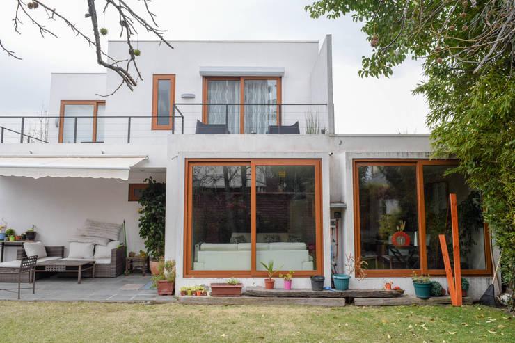 Fachada Norte y patio trasero: Casas unifamiliares de estilo  por Arqbau Ltda.
