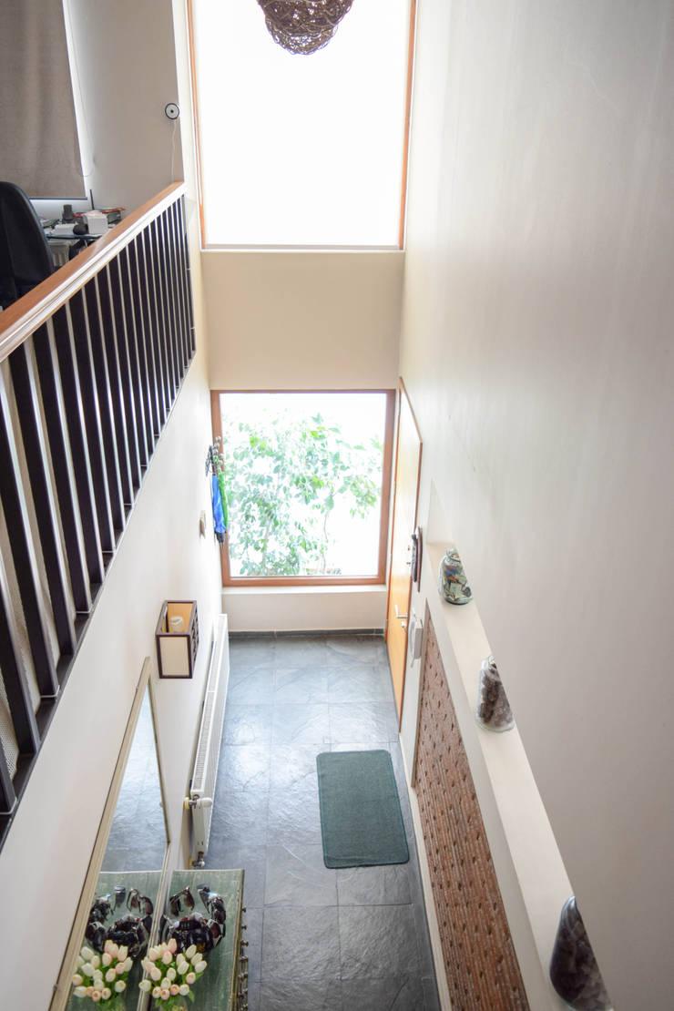 Vista interior, doble altura que comunica visualmente el 1º con el 2º piso: Pasillos y hall de entrada de estilo  por Arqbau Ltda.