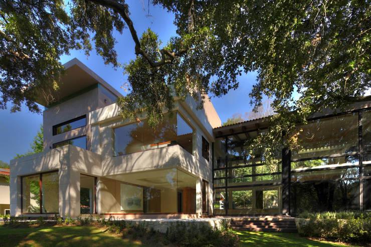 Fachada con vista al campo de golf: Casas unifamiliares de estilo  por Lazza Arquitectos