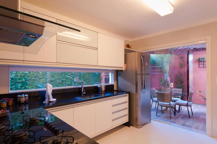 Cozinha com copa aberta para o jardim: Armários e bancadas de cozinha  por Bernal Projetos - Arquitetos em Salvador
