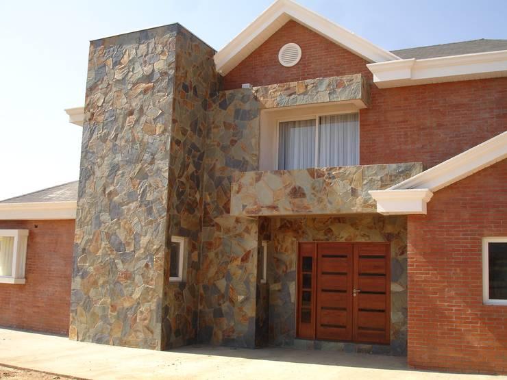 ACCESO ENCHAPADO: Casas unifamiliares de estilo  por ARKITEKTURA