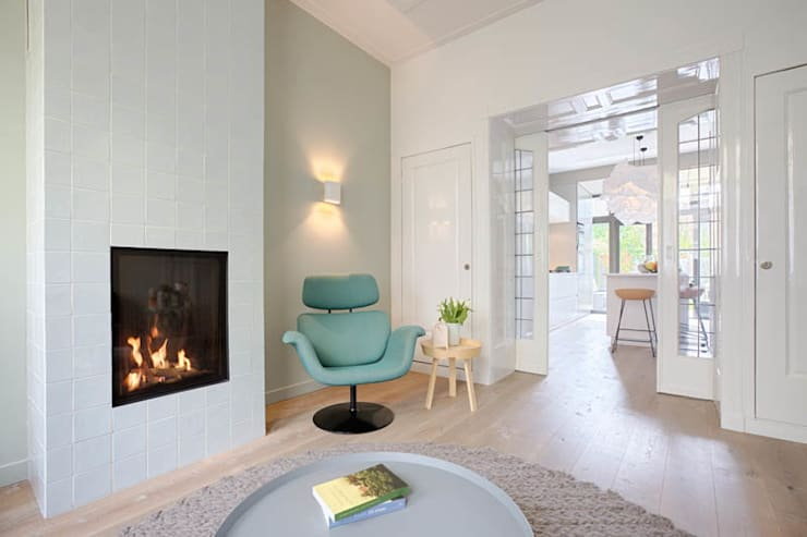 moderne woonkamer en suite met behaaglijke openhaard:  Woonkamer door StrandNL architectuur en interieur