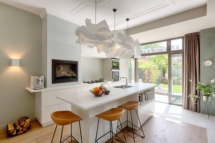 maatwerk keuken met openhaard en royale schuifpui naar de tuin:  Keukenblokken door StrandNL architectuur en interieur, Modern