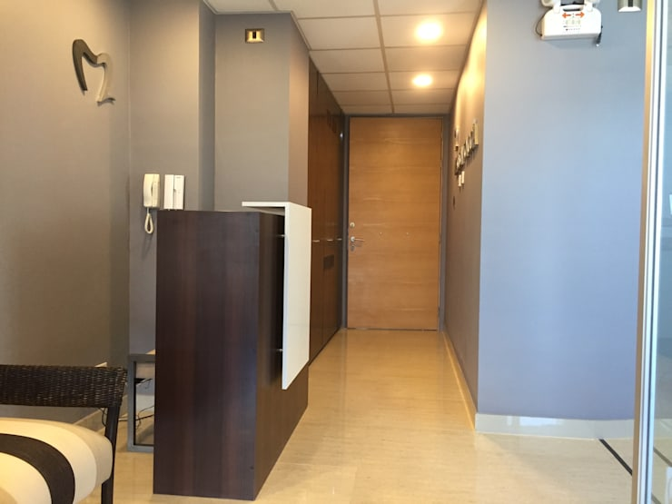 Hall de acceso y sala de espera con mueble recepción: Estudio de estilo  por Arqsol
