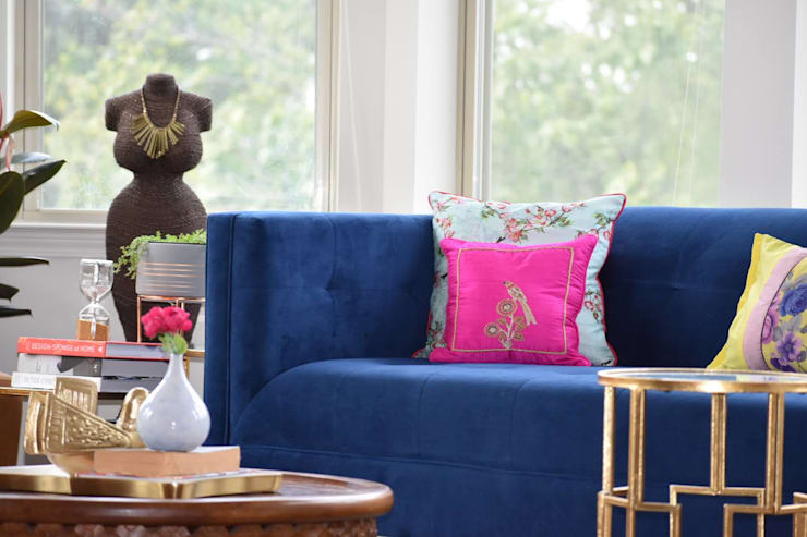 Beautiful Vignette of a decorative mannequin & blue velvet sofa:  Living room by Spaces Of Hue