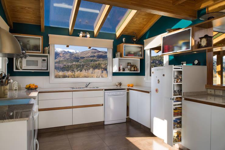 Cocina con iluminación natural y terminación en madera I Patagonia Log Homes: Cocinas a medida  de estilo  por Patagonia Log Homes - Arquitectos - Neuquén
