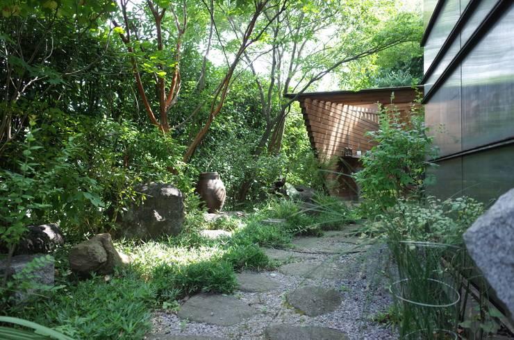 自然の中に建物を建てた様な庭: 株式会社高野設計工房が手掛けたアプローチです。
