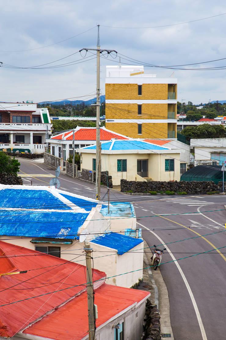 바닷가 집들 지붕색과의 어울림: 에이오에이 아키텍츠 건축사사무소 (aoa architects)의  다가구 주택,모던 벽돌