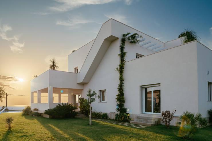 Vista laterale con scala esterna : Case in stile  di manuarino architettura design comunicazione