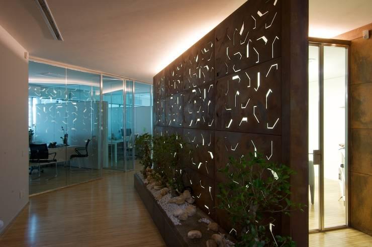 sala riunioni con dietro la zona ad uffici operativi: Complessi per uffici in stile  di Daniele Arcomano