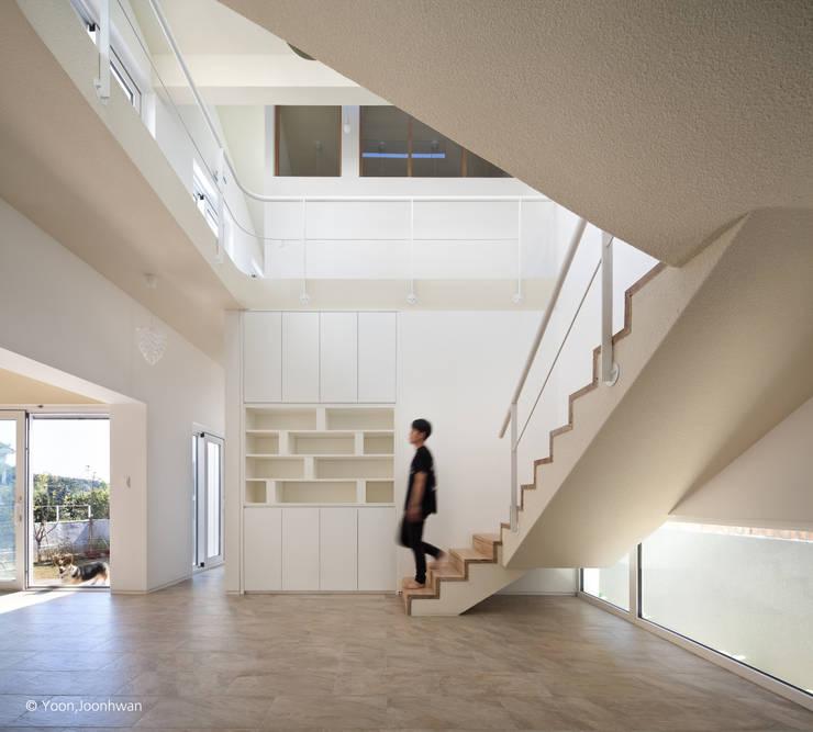 1층 계단실과 상부 보이드 공간: 건축사사무소 모뉴멘타의  거실