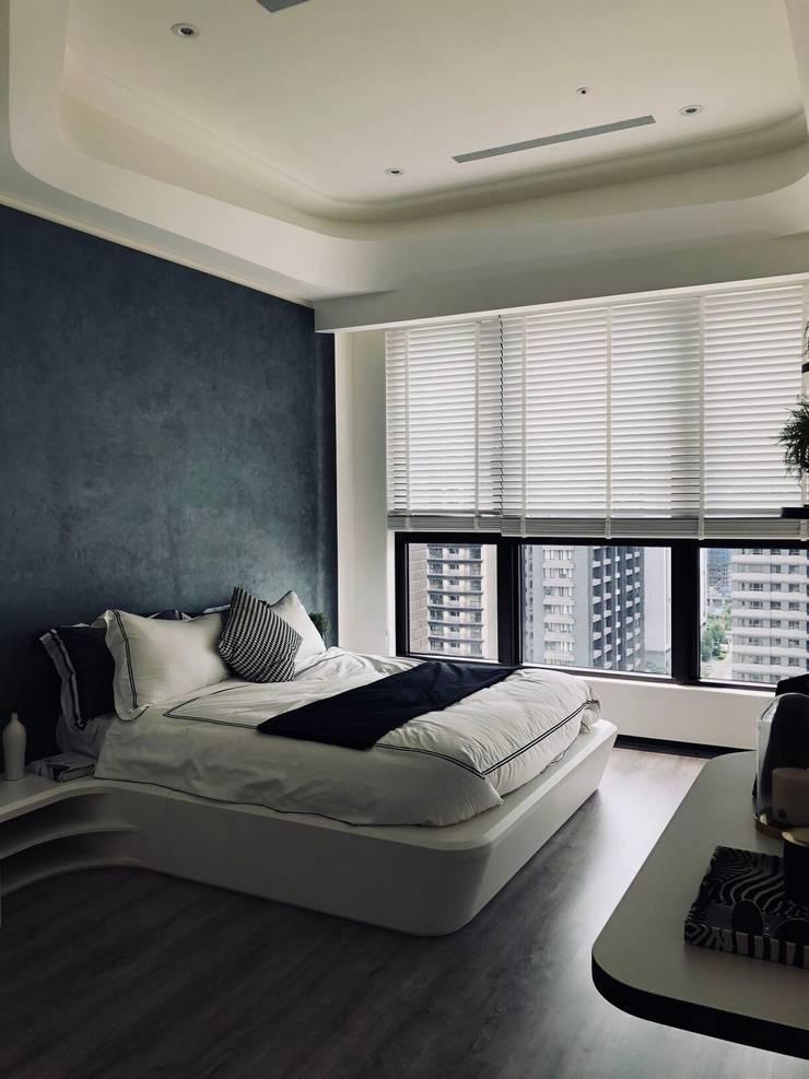 深藍色床頭牆漆呼應了住宅整體空間的時尚感:  臥室 by On Designlab.ltd