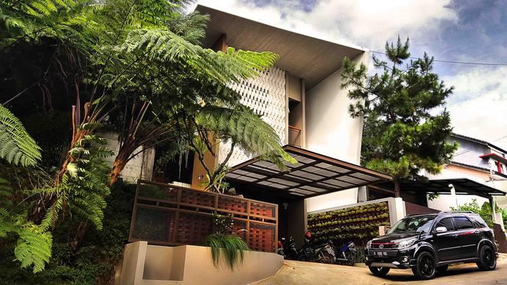 Facade rumah bergaya tropis kontemporer:  Rumah tinggal  by Mandalananta Studio