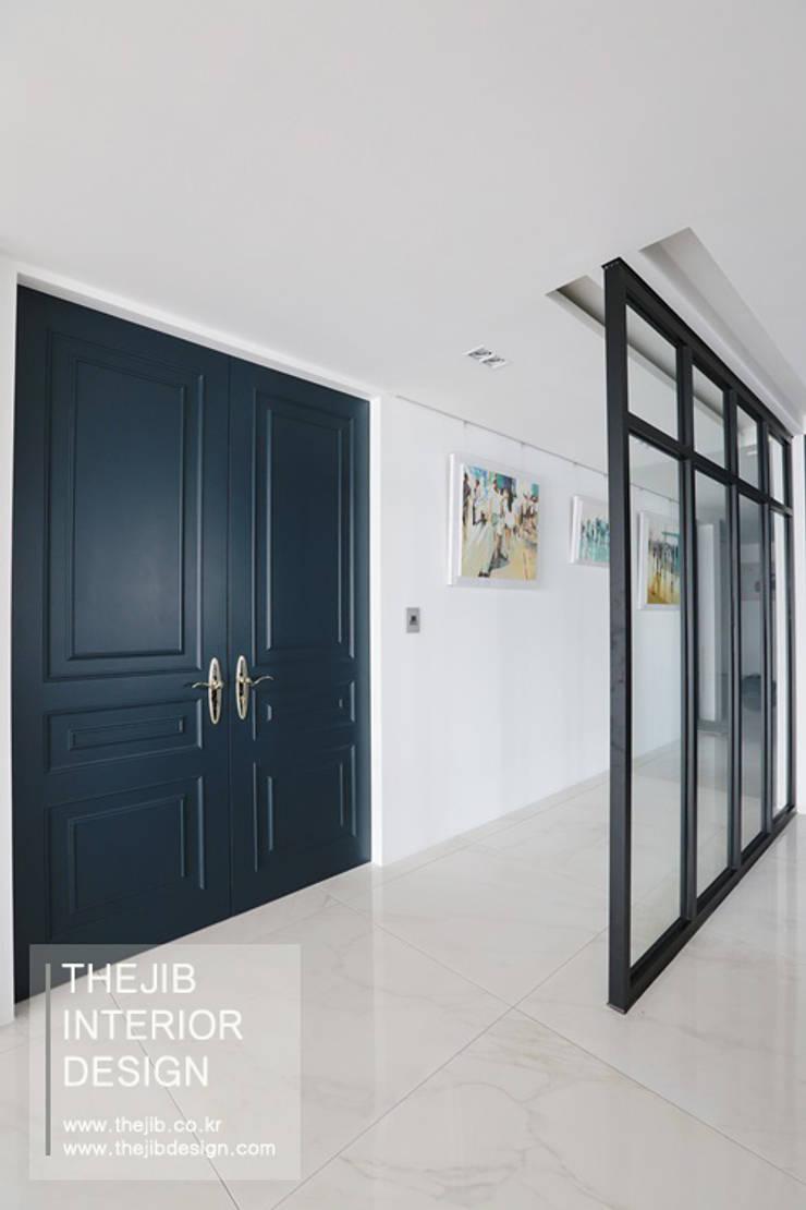 다크한 블루 컬러가 돋보이는 동부센트레빌 53평 아파트 인테리어: 더집디자인 (THEJIB DESIGN)의  거실,클래식