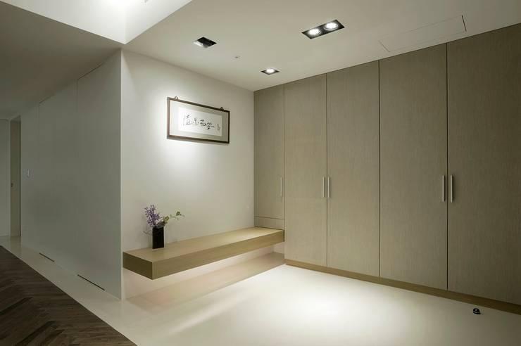 大片的收納櫃讓外出衣物與鞋子都能物歸其所:  走廊 & 玄關 by 直方設計有限公司