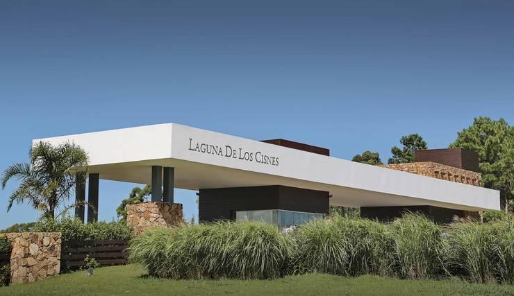 Ingreso al predio: Condominios de estilo  por Patagonia Log Homes - Arquitectos - Neuquén,