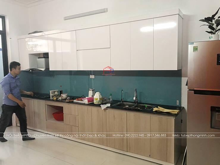 Màu trắng bóng kết hợp với màu vân gỗ tạo sự hài hòa cho bộ tủ bếp laminate nhà anh Linh:  Kitchen by Nội thất Hpro