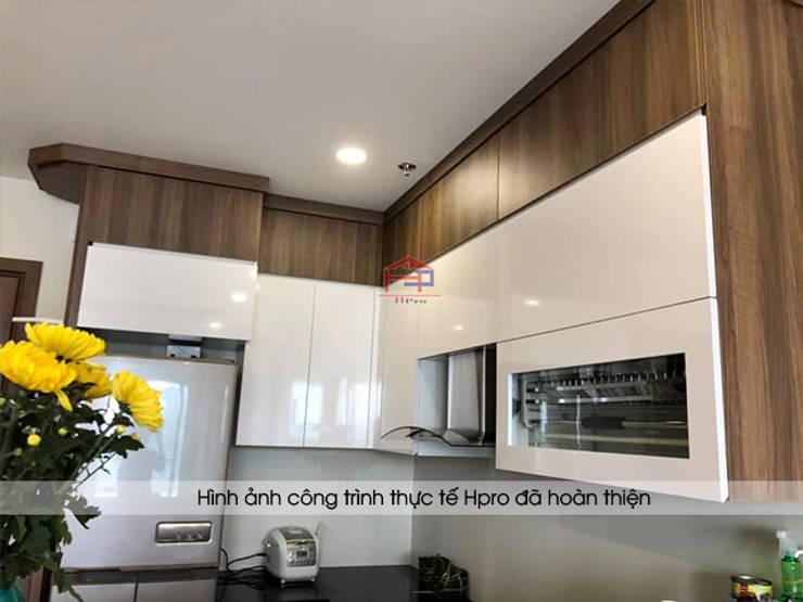 Tủ bếp laminate màu trắng bóng kết hợp với màu vân gỗ tạo sự sang trọng cho không gian nhà bếp của chú Việt:  Kitchen by Nội thất Hpro
