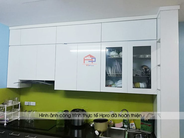 Màu trắng của hệ tủ bếp trên giúp không gian phòng bếp sáng và rộng hơn:  Kitchen by Nội thất Hpro
