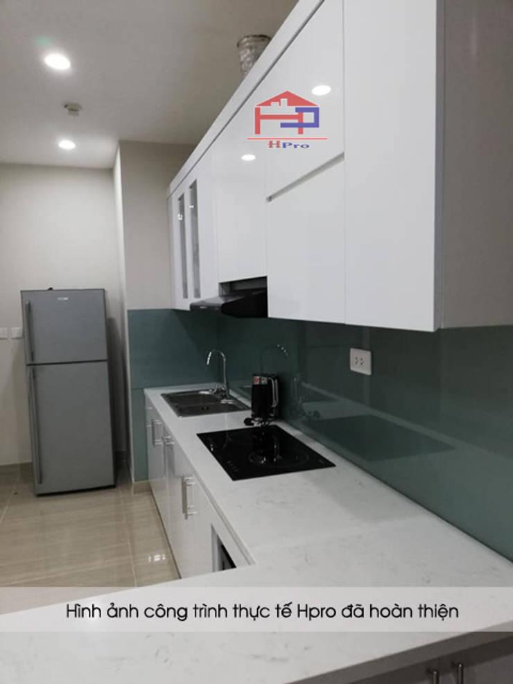 Tủ bếp acrylic màu trắng nhà chị Hiền có bề mặt mịn, phẳng và sáng bóng như gương.:  Kitchen by Nội thất Hpro