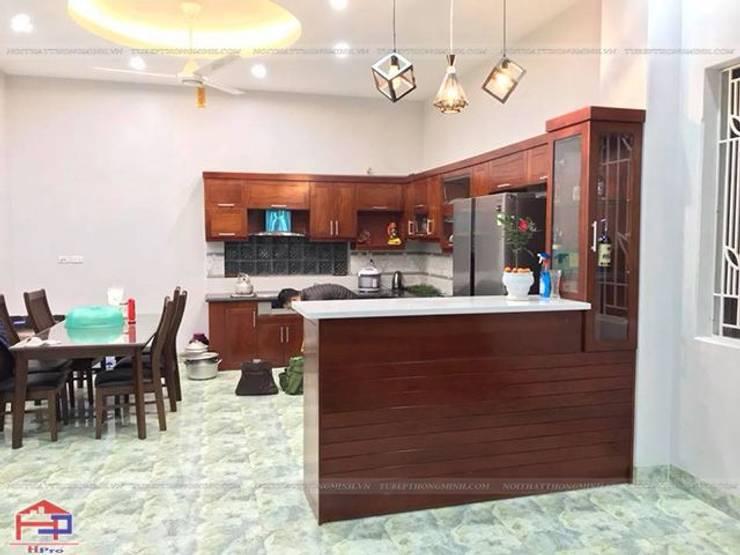 Ảnh thực tế bộ tủ bếp gỗ xoan đào kèm quầy bar mini nhà anh Cường ở Đông Anh:  Kitchen by Nội thất Hpro