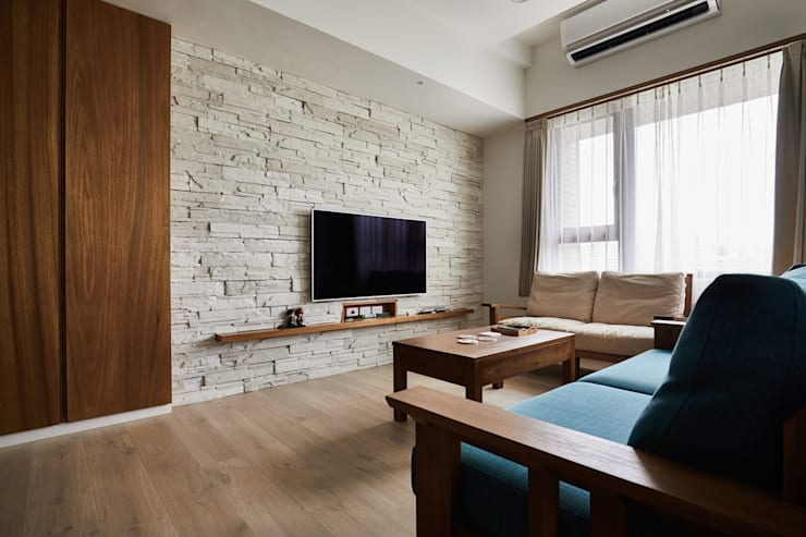 電視牆利用文化石來襯托出自然質感:  客廳 by 弘悅國際室內裝修有限公司